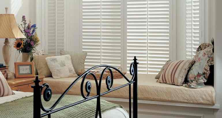 Polywood shutters in a modern bedroom bay window.