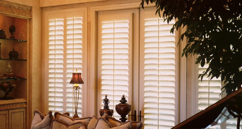 Plantation shutters on windows and door in Miami parlor