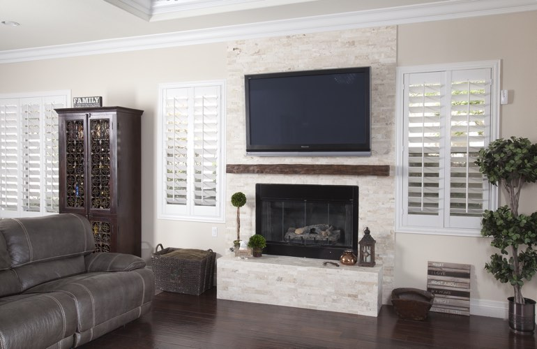 White plantation shutters in a Miami living room with plank hardwood floors.
