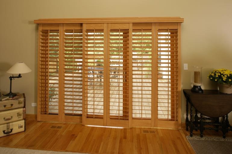 Wood shutters on sliding door going to back porch.