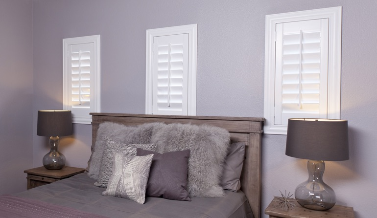 White plantation shutters in Miami bedroom windows.