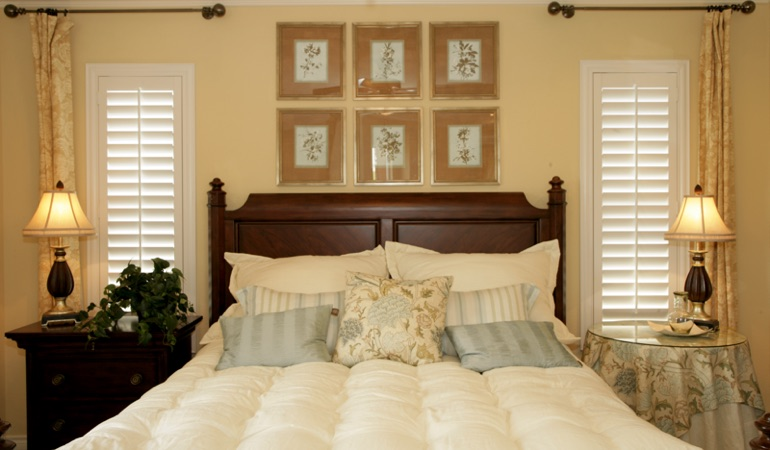 Bedroom with two tall plantation shutters on either side of bed in Miami