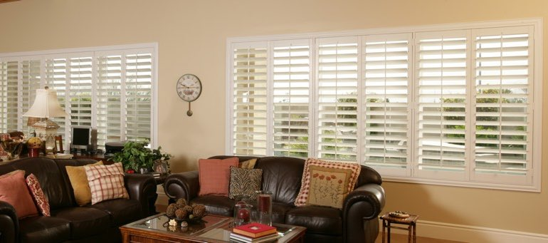 Wide window with interior shutters in Miami living room